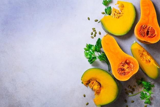 Couper la citrouille orange mûre avec des graines et des herbes en gris clair. concept d'aliments biologiques sains végétariens et crus, régime alimentaire.