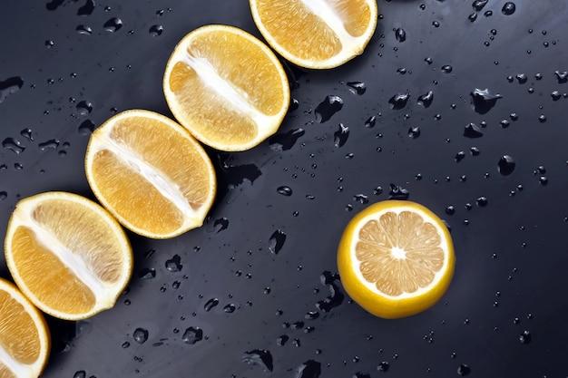 Couper en deux les citrons sur fond sombre