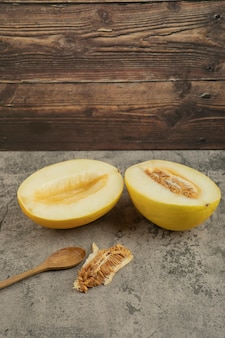 Couper en deux de délicieux melons jaunes sur une surface en marbre avec une cuillère en bois de côté.