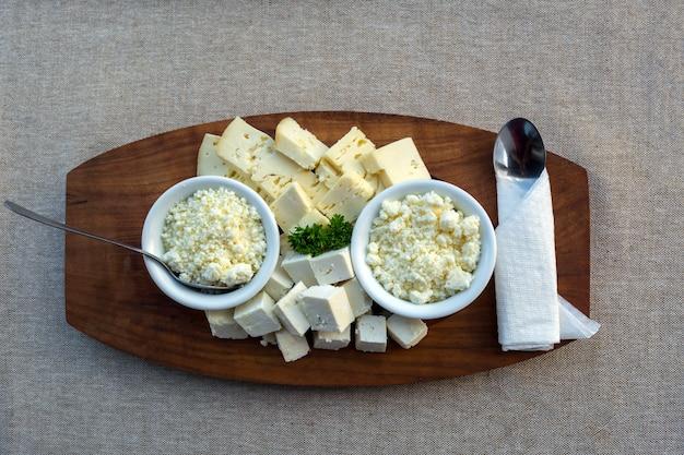 Couper différents fromages sur un plateau en bois