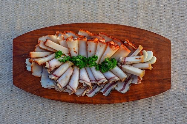 Couper du bacon frais sur un plateau en bois. concept d'un repas gras