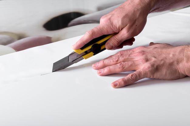 Couper du papier blanc avec un couteau