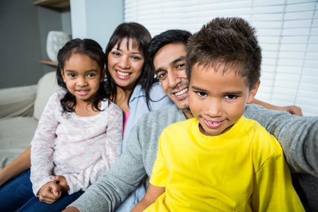 Couper de la famille en prenant un selfie sur le canapé dans le salon