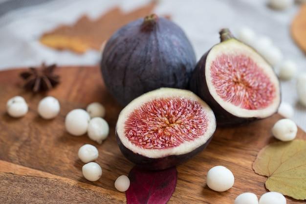 Couper les figues mûres savoureuses fraîches sur le bureau avec des baies de neige blanches, anis, feuilles sèches tombées, flou