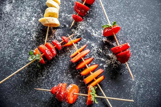 Couper les fraises et les bananes aux prunes sur une brochette avec du sucre en poudre sur fond gris