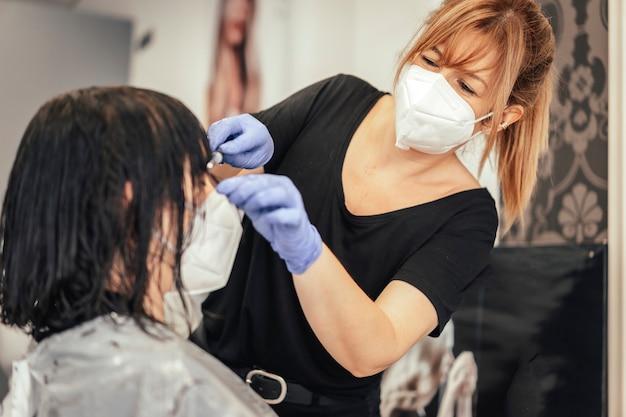 Couper la frange à un client avec des mesures de sécurité. réouverture avec des mesures de sécurité des coiffeurs dans la pandémie de covid-19