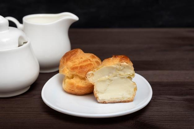 Couper le gâteau éclair sucré avec une garniture à la crème sur une assiette blanche. gâteaux de pâtisserie.