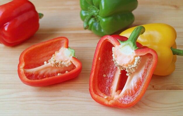 Couper gros plan de poivron rouge avec des poivrons tricolores sur table en bois