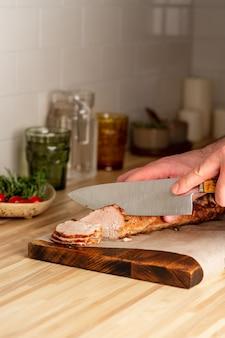 Couper l'homme méconnaissable avec un grand filet de porc cuit au four sur une planche à découper, vertical