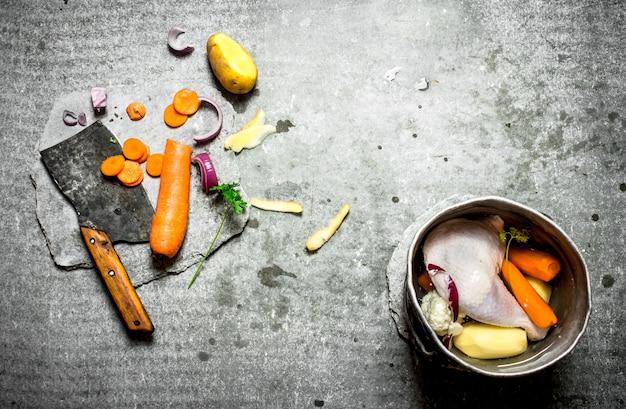 Couper les légumes pour la soupe au poulet sur table en pierre