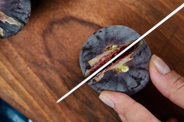 Couper à la main une figue sur une planche à découper en bois.