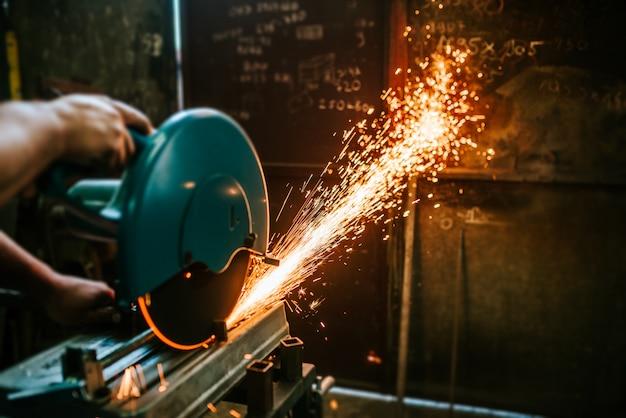 Couper un métal avec une scie à onglet avec une lame circulaire tranchante.