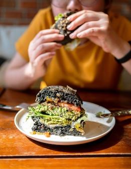 Couper la moitié du hamburger au charbon de brocoli et quinoa garni de guacamole, de salsa à la mangue et de salade fraîche servi sur une assiette blanche. repas végétalien créatif pour les végétariens.