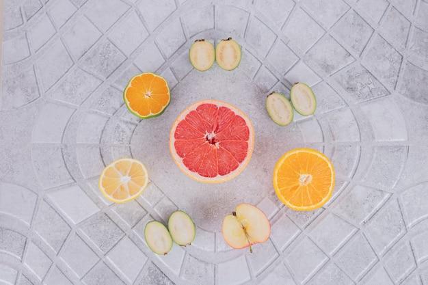 Couper la moitié des fruits frais sur une surface en marbre.