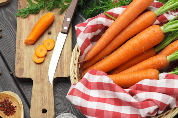 Couper en morceaux les carottes saines sur une planche à découper dans la cuisine