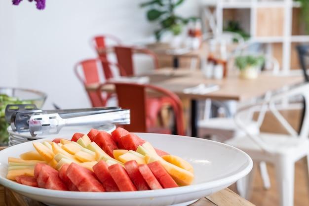 Couper les morceaux de melon d'eau et d'ananas dans un plat blanc le repas et les fleurs