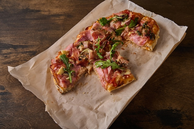 Couper en morceaux pizza romaine rectangulaire avec jambon prosciutto tomates mozzarella et roquette sur