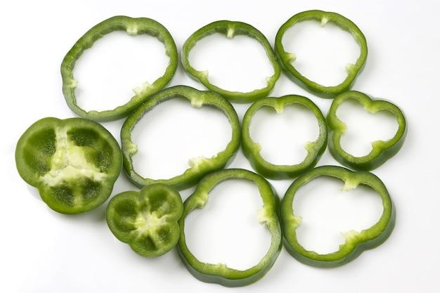 Couper en morceaux les poivrons verts sur fond blanc. légumes et aliments frais et sains