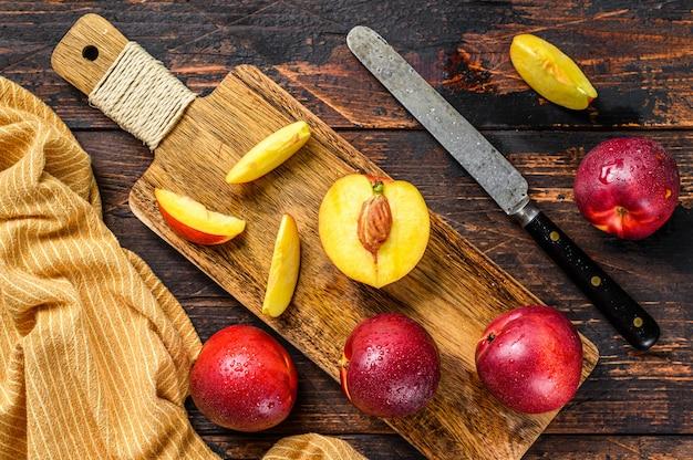 Couper les nectarines sur une planche à découper en bois. .
