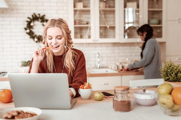 Couper la nourriture derrière. femme blonde aux cheveux longs mordant des bâtons de légumes tout en travaillant avec un ordinateur portable sur la table de cuisine