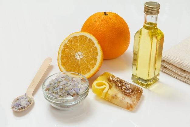 Couper l'orange avec un entier, une serviette éponge, une bouteille d'huile d'aromathérapie, du savon fait maison et une cuillère en bois avec du sel de mer sur la surface blanche