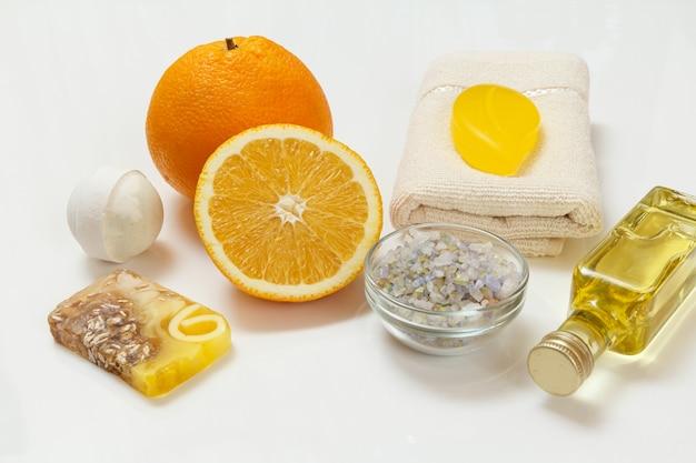 Couper l'orange avec une entière, une serviette éponge, une bouteille d'huile d'aromathérapie, du savon fait maison, une bombe de bain et un bol en verre avec du sel de mer sur la surface blanche