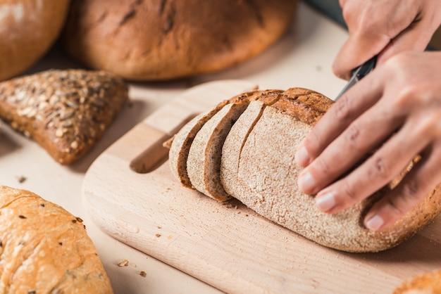 Couper le pain avec un couteau sur une planche à découper à la main