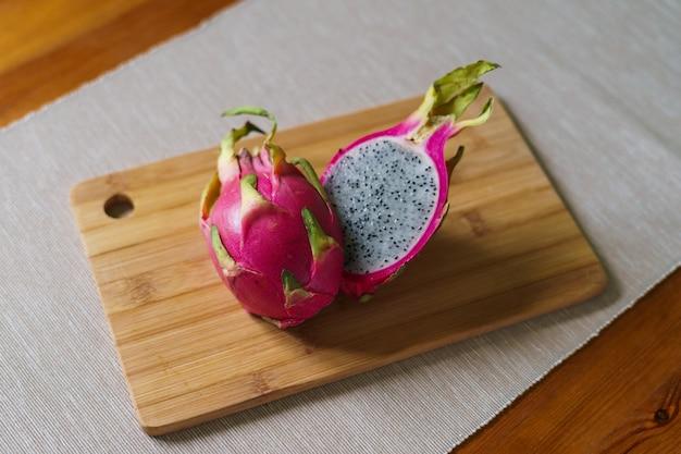 Couper le pitaya frais ou le fruit du dragon sur une table en bois
