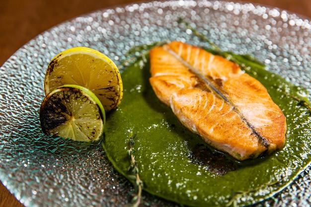 Couper le poisson au citron et sauce dans une assiette en verre sur une table en bois dans un restaurant de luxe
