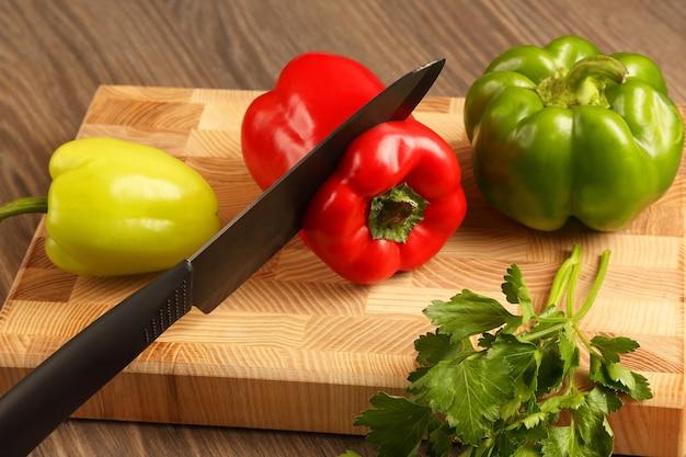 Couper le poivre sur la planche de cuisine