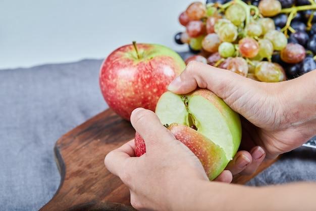 Couper une pomme en deux moitiés et grappe de raisin sur une planche de bois. photo de haute qualité