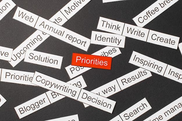 Couper les priorités d'inscription sur papier sur fond rouge, entourées d'autres inscriptions sur fond sombre. concept de nuage de mots.