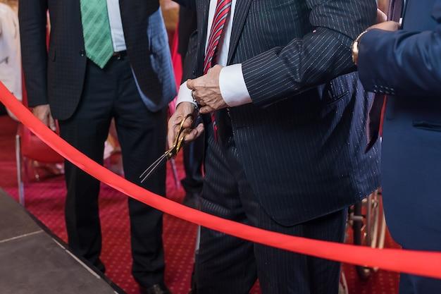Couper un ruban rouge avec des ciseaux pour une nouvelle entreprise commerciale ou une cérémonie d'ouverture