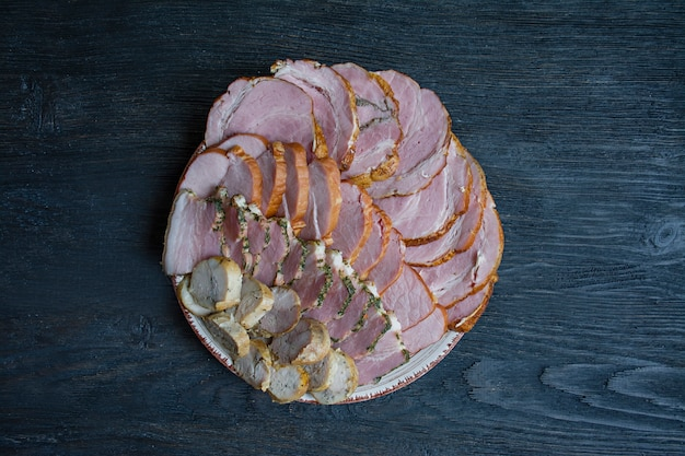 Couper des saucisses et de la viande séchée sur la table de vacances