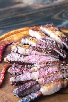 Couper le steak de boeuf sur la planche de bois