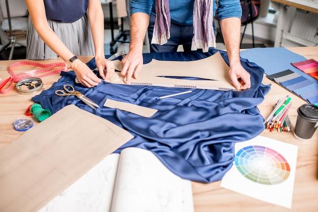 Couper le tissu bleu sur la table pleine d'outils de couture. vue rapprochée sur les mains et le tissu sans visage