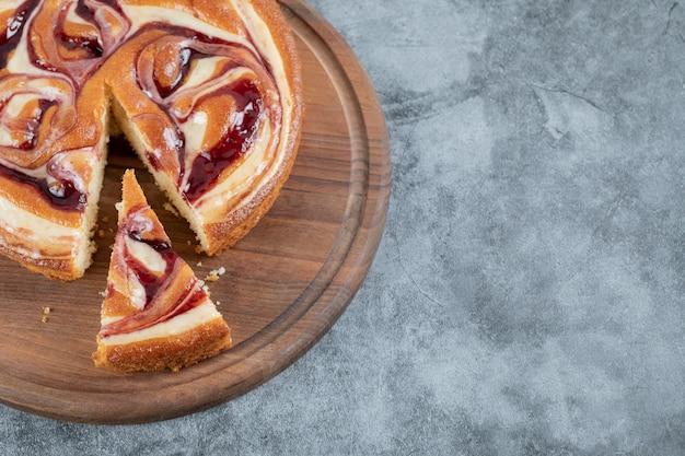 Couper une tranche de gâteau aux fraises sur une planche en bois.