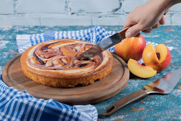 Couper une tranche de tarte au sirop de chocolat sur une planche de bois.