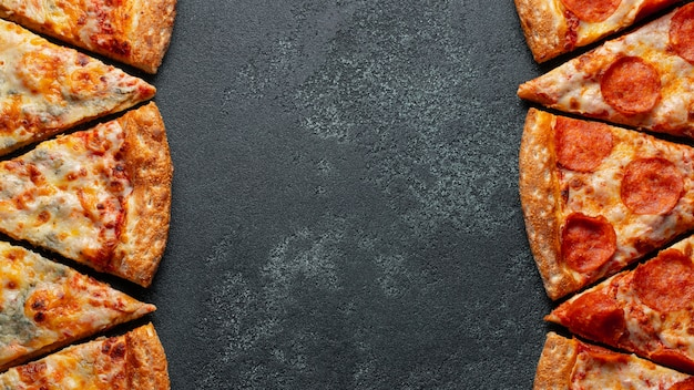 Couper en tranches de délicieux pepperoni à la pizza fraîche et une pizza four cheese sur un fond sombre.
