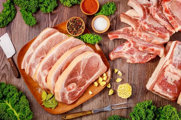 Couper la viande de porc dans l'os et la poitrine de porc sur une table en bois.
