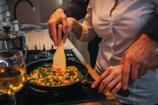 Couper la vue et fermer. homme aidant la femme à préparer le dîner. il tient sa main sur la sienne. ils se tiennent ensemble au poêle.