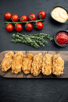 Coupes d'ailes de poulet panées frites épicées sur fond noir