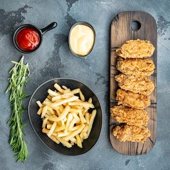 Coupes d'ailes de poulet panées sur table grise, vue du dessus.