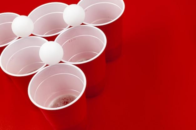 Coupes et boule en plastique sur fond rouge. jeu de bière pong