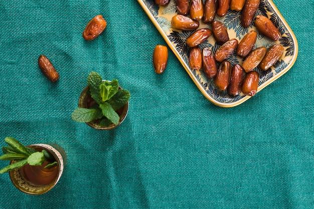 Coupes avec des brindilles de plantes et de fruits secs sur un plateau