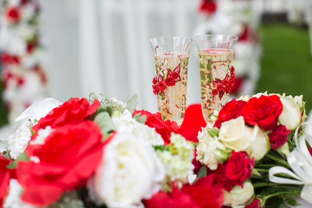 Les coupes de champagne. cérémonie de mariage à l'extérieur. bouquet de fleurs rouges.