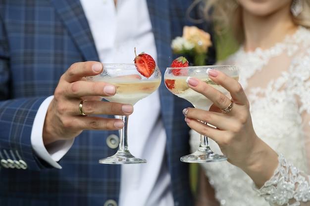 Les coupes de champagne dans les mains des nouveaux mariés.