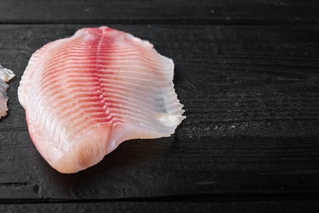 Coupes de filet de poisson blanc cru, sur table en bois noir