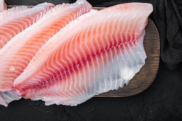 Coupes de filet de poisson blanc cru, sur tableau noir, vue de dessus