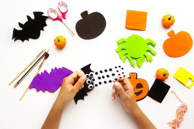 Coupes de papier pour halloween. papier découpé à la main. citrouilles, chauves-souris et araignées ciseaux et colle. sur fond clair. vue de dessus. mise à plat. diy. pas à pas